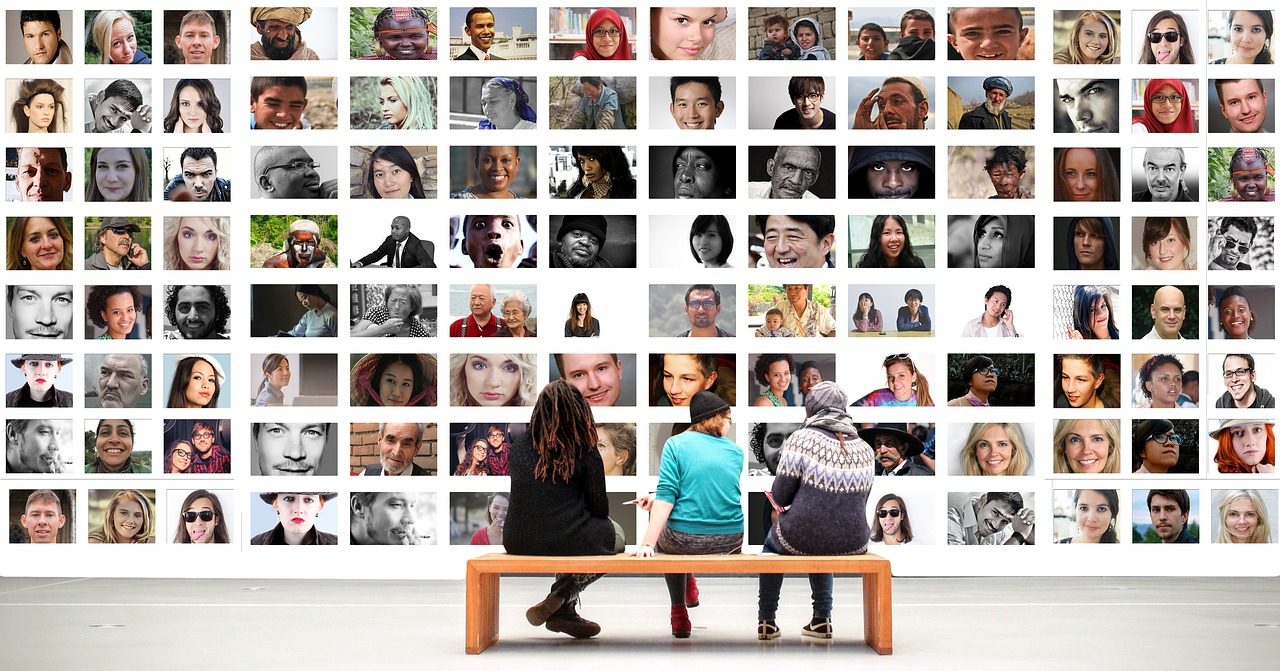 three people sat on a bench looking at a large photo gallery of human faces.